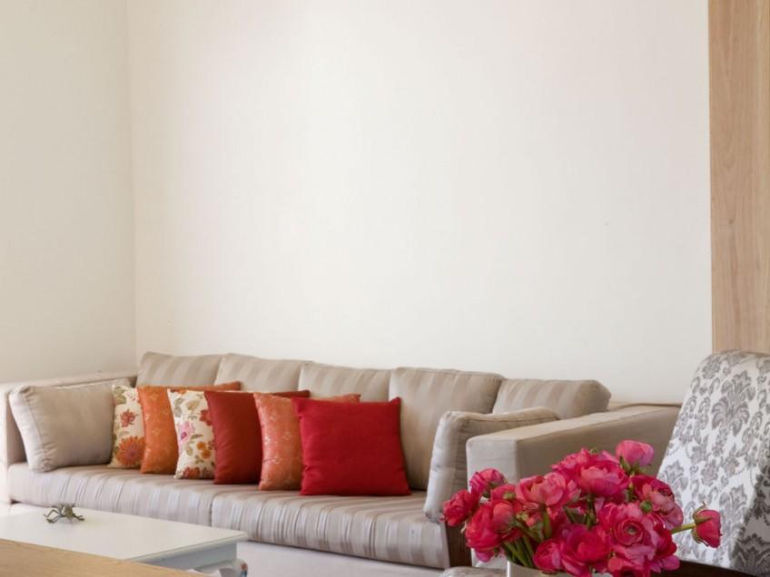 כל הצבע בסלון מתקבל משורה של כריות נוי בגוונים חמים, מה שטקסטיל יכול לעשות
